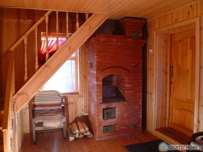 Кирпичная печь для обогрева дачного дома была размещена под лестницей